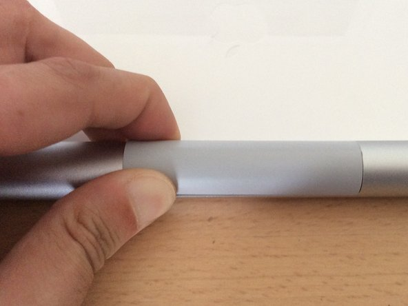 Squeeze on each end of the plastic cover, lifting one side up.