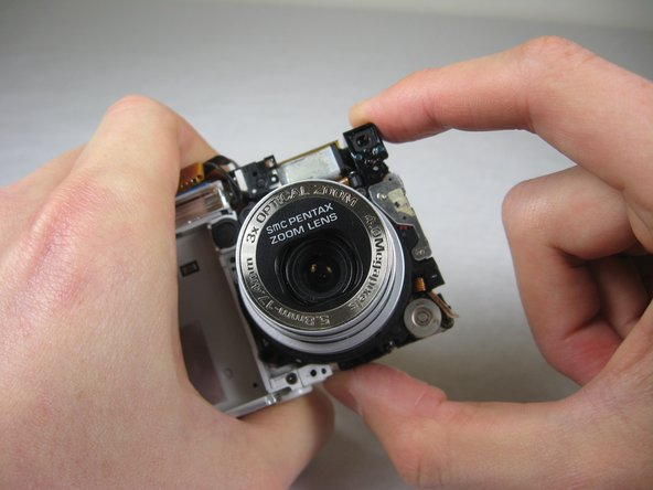 Image 1/3: Carefully twist the lens assembly away from you. You will be turning your hand clockwise.