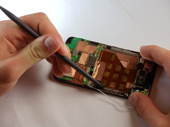 Using a spudger, begin to pry the copper colored board in the middle away from the phone to loosen it.
