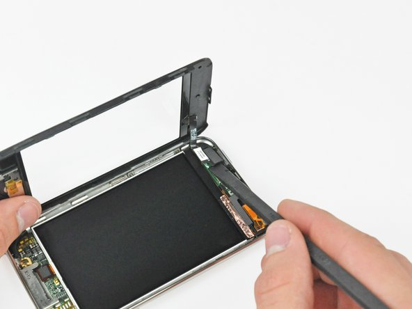 Use the flat end of a spudger (or an opening tool) to pry the touch screen cable connector up off the upper logic board.