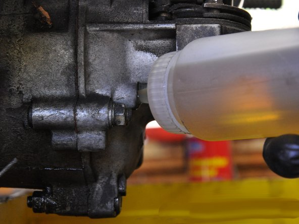 Put the nozzle of the oil bottle into the oil fill hole and pour or squirt oil into the engine until it is filled level with the fill hole.