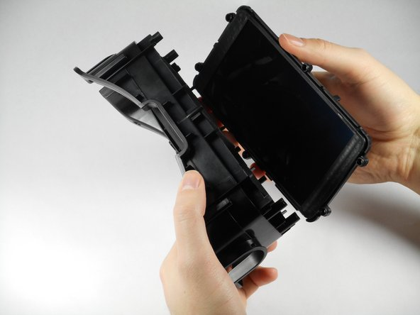 Image 3/3: Gently lift the plastic screen holder and display screen away from the remaining piece of the faceplate.