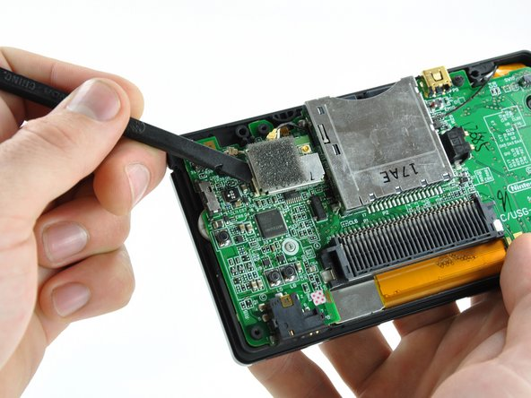 Use the flat edge of a spudger to pry the Wi-Fi board connector straight up from its socket on the motherboard.