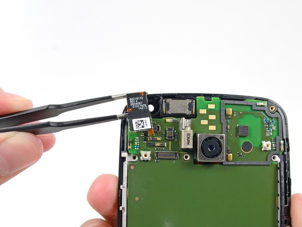 Image 1/3: After selecting our favorite pair of [product|IF145-060|precision tweezers], we remove the 2 MP front-facing camera from the Moto X.