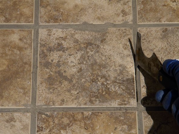 Use a painter's tool or putty knife to remove the grout from around the cracked tile.