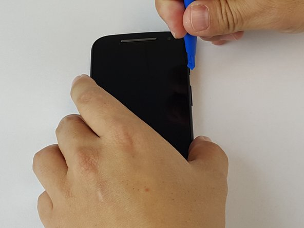 Using the small plastic opening tool, pry and slide all the way around the phone while carefully lifting up on the display.