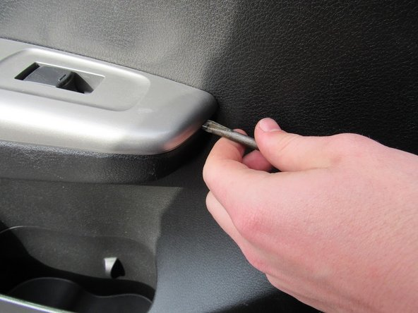 Use the flathead screwdriver to pry off and remove the panel over the door handle.