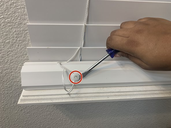 """Using the 7/32"""" flathead screwdriver, gently lift up the buttons located on the bottom rail of the blinds."""