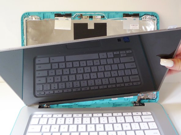Grab the screen by its unlocked tabs and tilt it down and away from the screen assembly, laying it down.