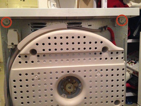 Entfernen Sie die Deckplatte des Trockners. Dazu sind zwei Sechskantschrauben, Schlüsselweite 7mm (im Bild oben recht und oben links) zu entfernen und dann der Deckel nach hinten schieben und gleichzeitig abheben (der Deckel ist vorne mit zwei Haken eingehängt)