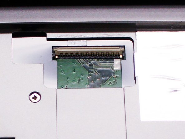 Flip up the ZIF connector holding the ribbon cable on the contact as shown in the two pictures and then gently disconnect the  ribbon cable.