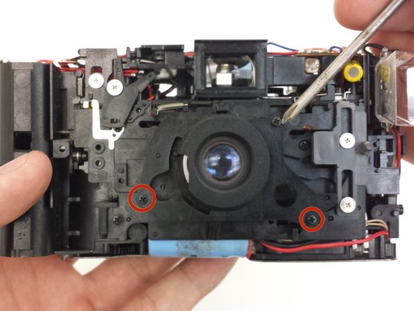 The lens is only attached to the main camera body. Set the front and back covers aside.