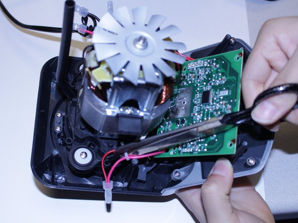 Using a pair of scissors, cut the zip ties holding the power wires in order to give the circuit board mobility.