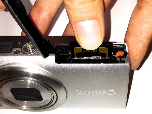 The memory card is stored behind the battery on the side opposite of the lens as outlined by the red rectangle in the picture.