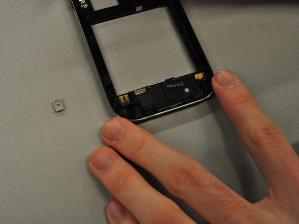 Use the spudger to pry out the grey rubber rectangular component from the main case.
