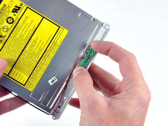 Image 1/1: Peel the reed switch board from the optical drive.  It is held in place with double stick tape.