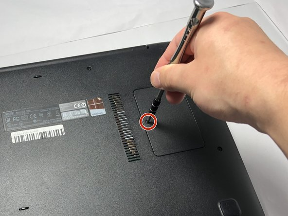 Remove the Phillips #0 screw holding the RAM access panel in place.