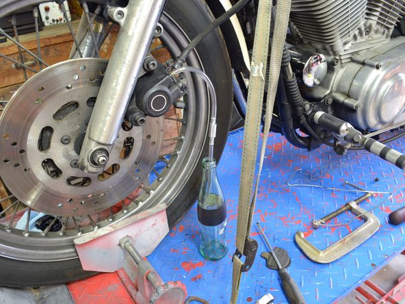 Image 1/2: Bleeding the brake lines is a whole-body effort. You will need to use one hand to pump the brake handle and one hand to maneuver a wrench on the brake bleed valve.