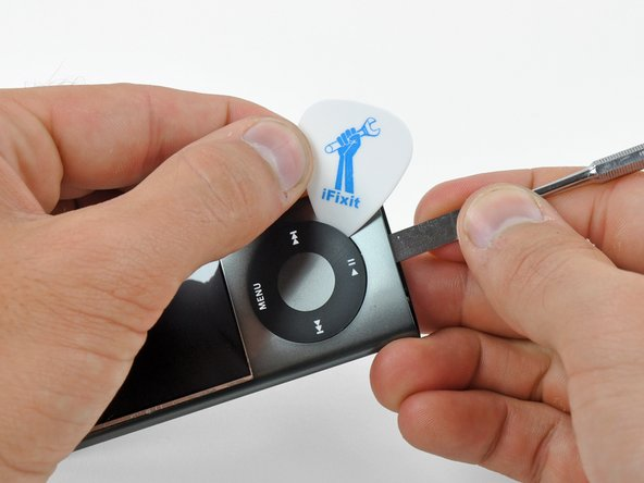 Image 1/2: Pry up the edges of the click wheel with the guitar pick until the click wheel comes free from the case.