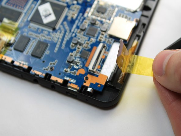 Image 3/3: Gently pull the tape attached to the ribbon cable to remove the cable from its socket.