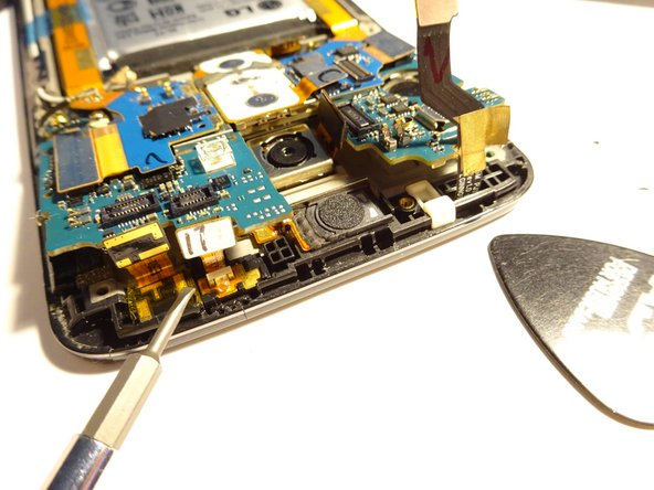 Using spudger/guitar pick/fingers, gently tilt the top of the motherboard up.