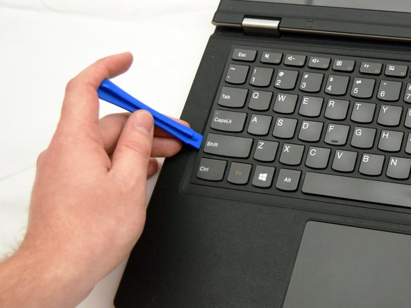Carefully run the tool around the top and sides of the keyboard to pop out the 9 tabs holding in the keyboard.