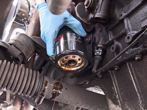 Maneuver the oil filter away from your engine and out of the car, trying your best not to spill oil everywhere.