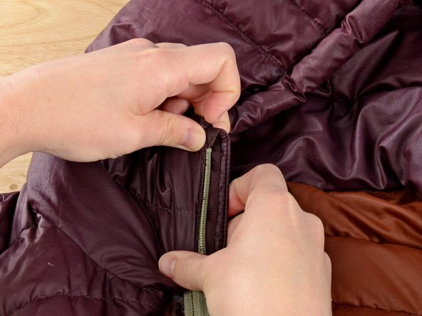 Reinsert the zipper and webbing into the jacket, aligning the edge of the jacket fabric with the zipper teeth.