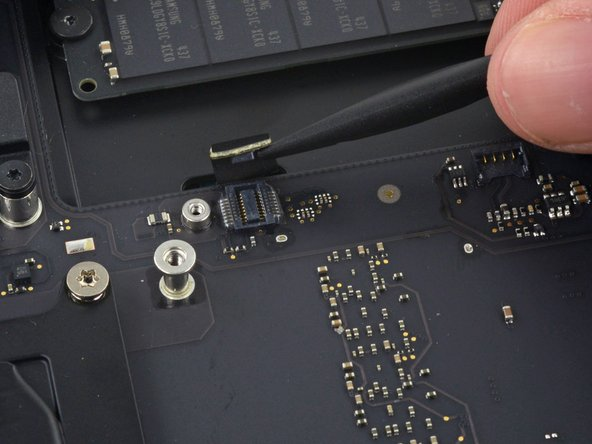 Use the flat end of a spudger to lift the SATA cable connector up off of its socket on the logic board.
