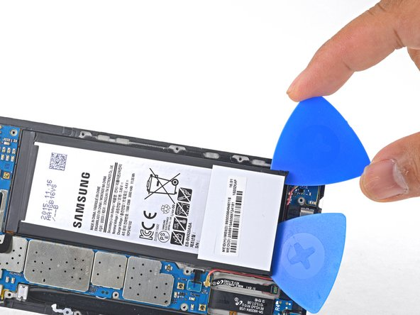 Slide an opening pick up the side of the battery to break apart any remaining adhesive.