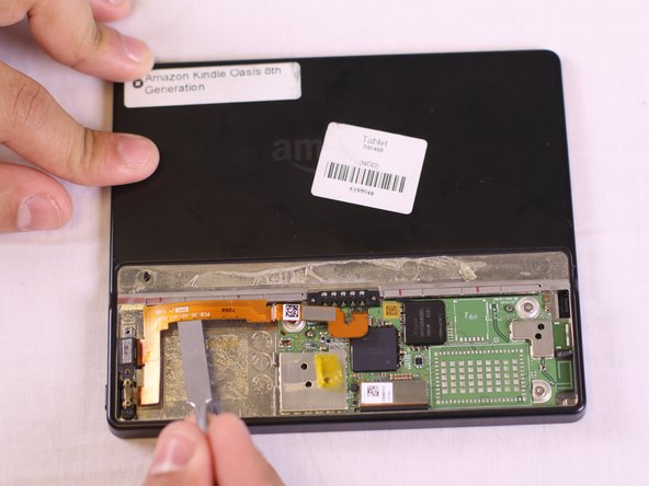Using the metal spudger, tweezers, and your finger tips, gently lift the orange power bridge connector off of the motherboard first and then off of the kindle.