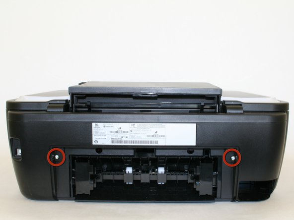 Locate the two screw holes that connect the two cylindrical extensions from the top portion of the scanner unit to the printer.