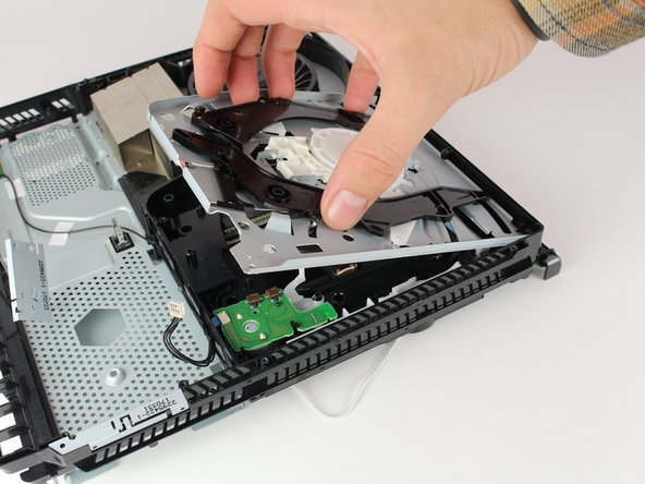"Remove the disk drive out by pinching on either side of the two black plastic ""claws"" and lifting up with your hand."