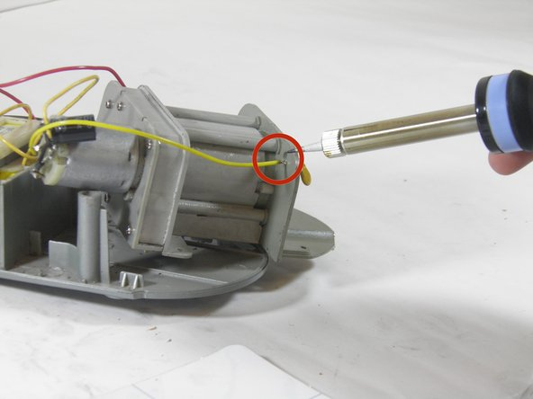 Image 1/1: Using a soldering iron, de-solder the sensor wire from the sensor bracket. Be careful to avoid melting the plastic components while soldering.