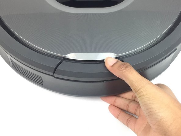 Press the large button on the Roomba that is located closest to you.