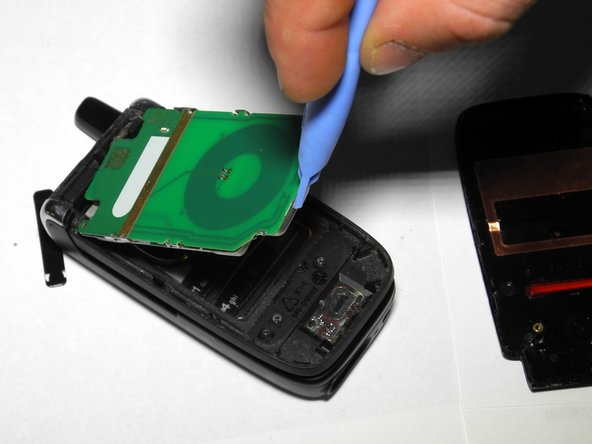 Use a plastic opening tool to pry the LCD circuit board up and out of the phone.
