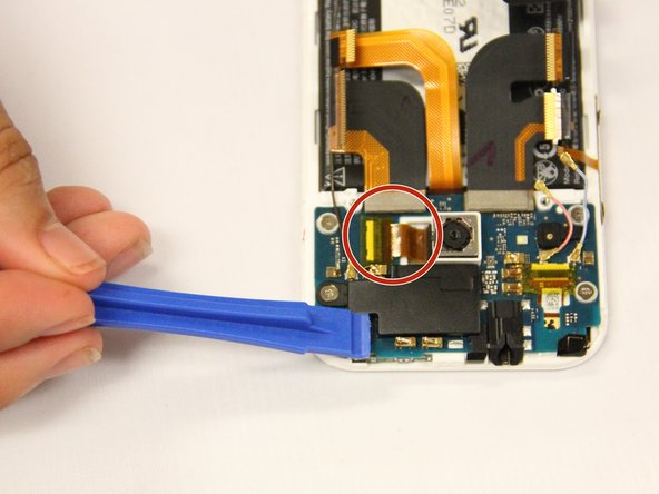 Remove the gold tape at the top right corner of the phone and disconnect the ribbon wire from the circuit board.