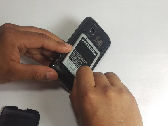 Using your fingernail or nylon spudger, remove the battery by lifting upward in the recess of the bottom right corner.
