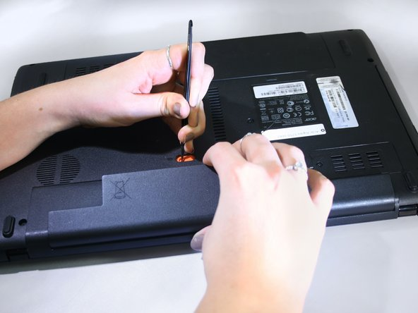 While holding the orange switch in place, lift the battery by the lip and pull it away from the laptop.