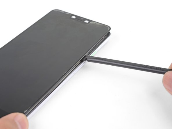 The screen is still adhered to the frame by a large adhesive pad near the center of the screen.