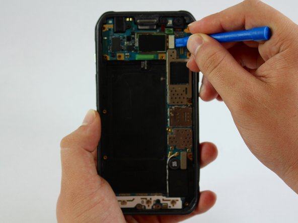 Use a plastic tool to undo the connection of the rear camera from the motherboard.