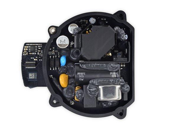 Le matériel de la carte gérant l'entrée du courant (AC-in) est inondé d'époxy, probablement pour empêcher que les folles vibrations le décollent. Le courant est distribué vers la carte en forme d'anneau via des chevilles conductrices genre Mac Pro.