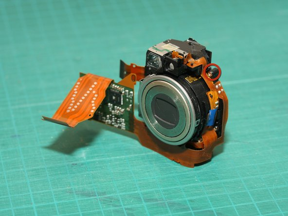 Image 2/2: The optical viewfinder can be separated from the lens module - however it's still joined by a flat flex ciruit - be careful not to damage this flex circuit; just leave the viewfinder dangling to the side.