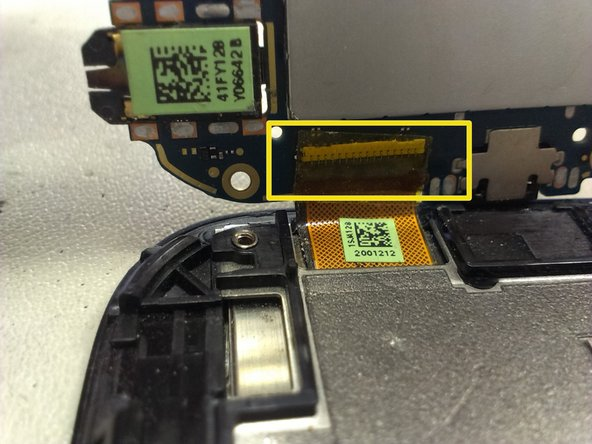 Image 3/3: Once its done, lift by one side the main board, and you can see the LCD connector. Open the white tab by lifting it up at the edge, and remove the flat cable.