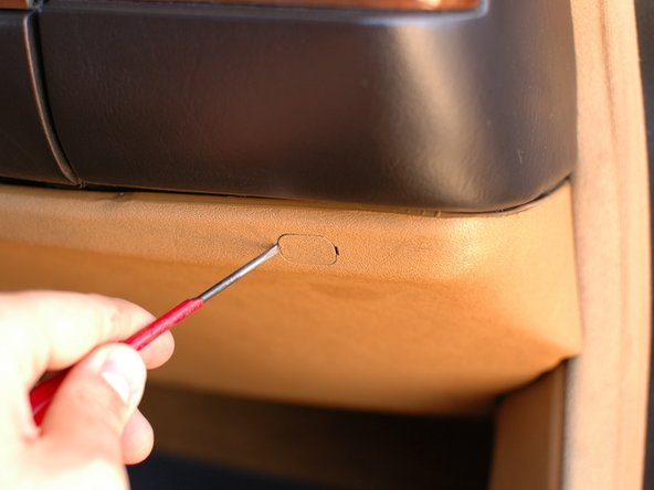 Begin by gently prying out the covers for the screws on the upper edge of the kick panel.