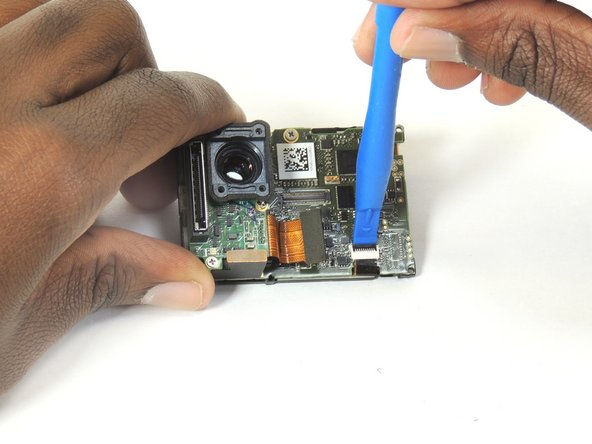 Image 3/3: Using the plastic opening tool, unclip the LCD ribbon from the motherboard.