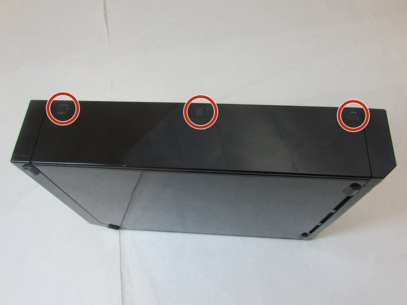 Use tweezers to remove the three black square stickers on the top of the console by prying under and gently pulling up to expose three  screws.