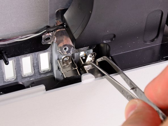 A pair of tweezers is helpful to remove and put the ports back in place. First insert the lower tab into the bracket on the outer case, then fasten the screw to secure the jack to the outer case.