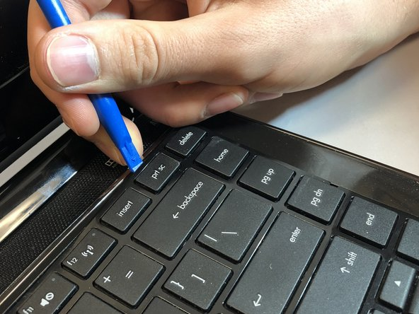 Using a plastic opening tool, pry up on the upper edge of the keyboard.