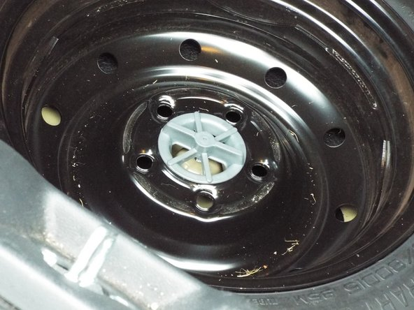 Turning counterclockwise, unscrew and remove plastic place holder in center of spare tire.